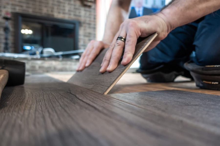 man installing engineered laminate wood floring indoor